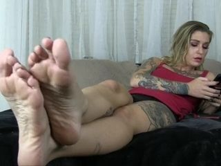 Kleio Valentien overlooks you while she plays on her smartphone she swings her soles